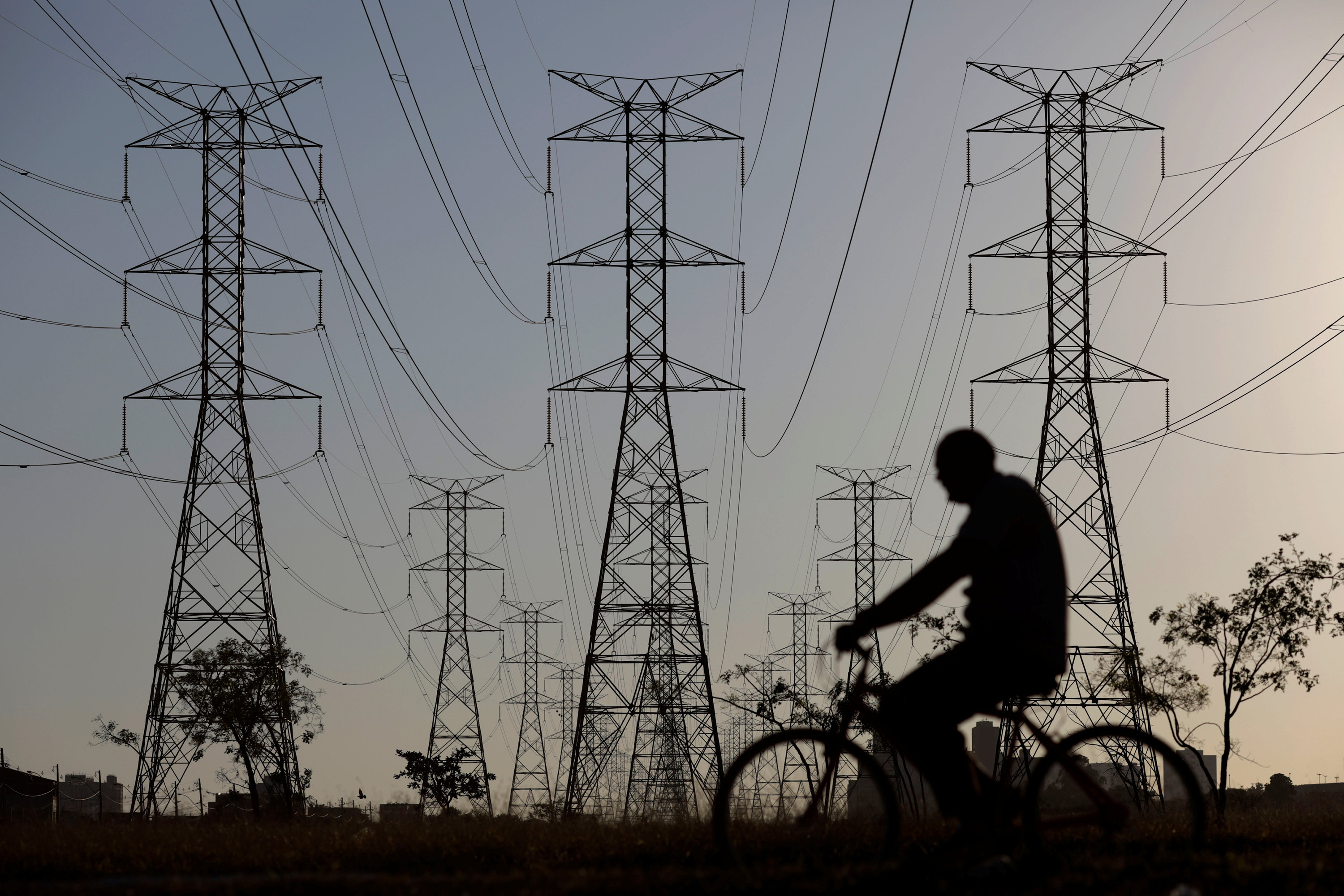 A man rides a bicycle near power lines connecting pylons of high-tension electricity, in Brasilia, Brazil  August 31, 2017. REUTERS/Ueslei Marcelino